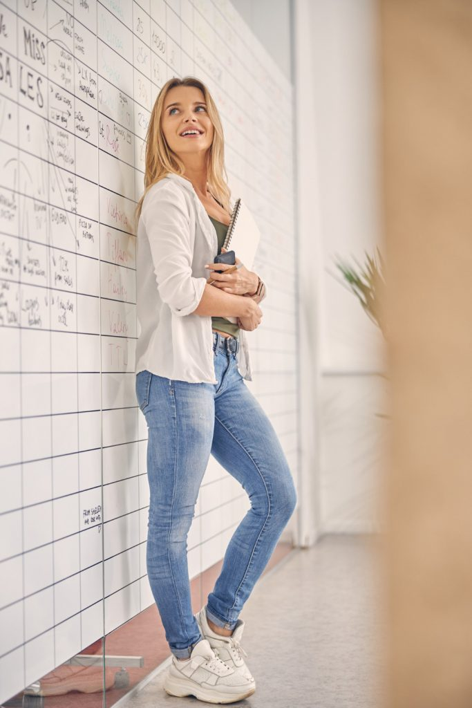 beautiful-female-worker-looking-planner-whiteboard-smiling-while-holding-sketchbook-smartphone